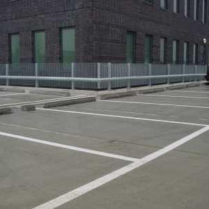 Buisconstructie lang de rand van een parkeerterrein voorzien van hekwerk
